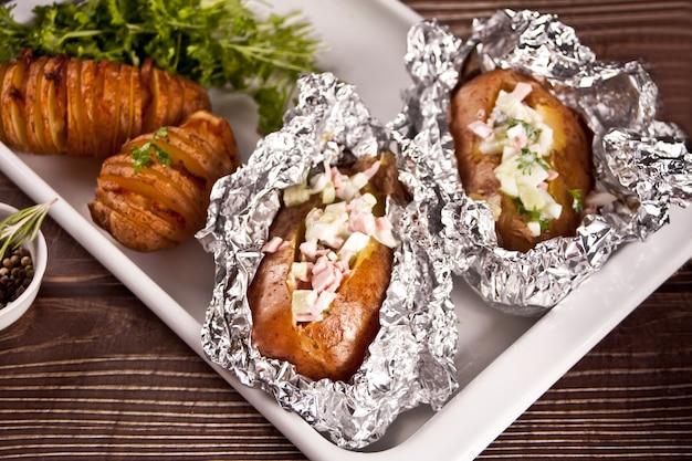Amerykańskie tradycyjne domowe ziemniaki hasselback i nadziewane ziemniaki ze świeżymi ziołami i bekonem. widok z góry.