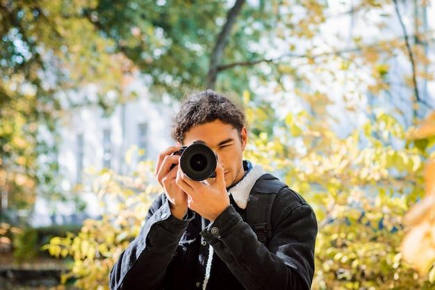Ameteur fotograf robi zdjęcia w parku miejskim