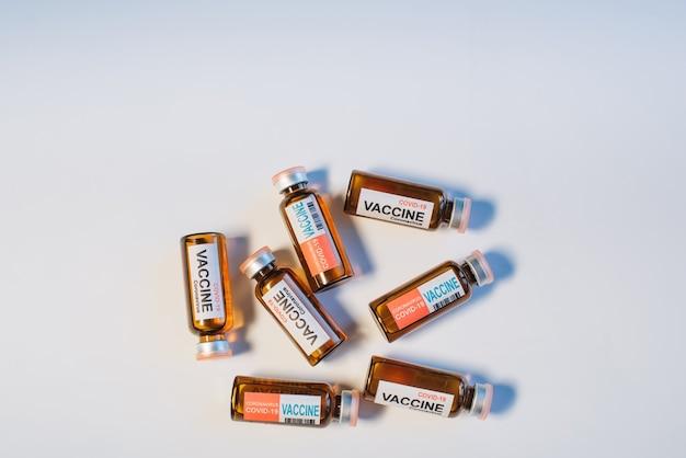 Ampułki różnych szczepionek przeciwko koronawirusowi leżą losowo na białym stole, zbliżenie. tło covid-19