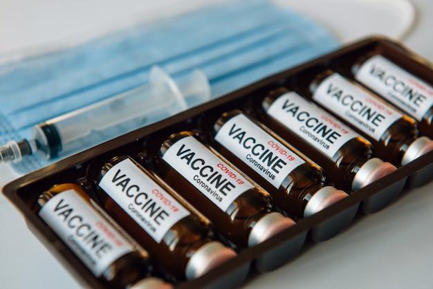 Ampułki ze szczepionką koronawirusową covid-19 w pudełku, rozmyte tło, zbliżenie. fiolki z lekiem, etykietą, strzykawką, maską medyczną, selektywne skupienie.