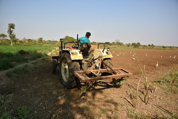 Amravati, maharashtra, indie - 03 lutego 2017: niezidentyfikowany rolnik w ciągniku przygotowującym ziemię do siewu z kultywatorem łożowym.