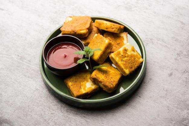 Amritsari paneer tikka z kostek twarogu zanurzonych w cieście z besanem, chat masala i przyprawami i płytko smażona na patelni, podawana z ketchupem