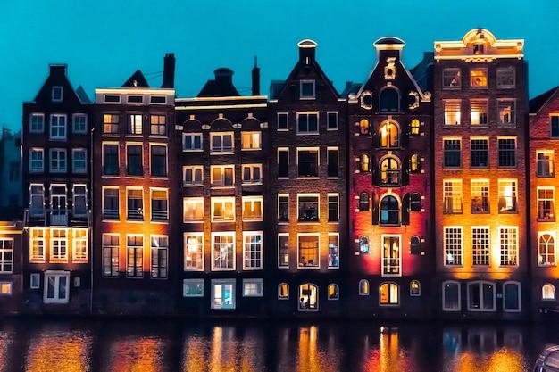 Amsterdam, holandia, europa tradycyjne stare wąskie domy i kanały w amsterdamie, stolicy holandii w jesienną noc. zdjęcie wysokiej jakości