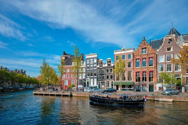 Amsterdam z widokiem na kanał z mostem boad i starymi domami