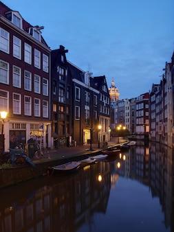 Amsterdamski kanał amstel z typowymi holenderskimi domami i domkiem z łodzi wieczorem