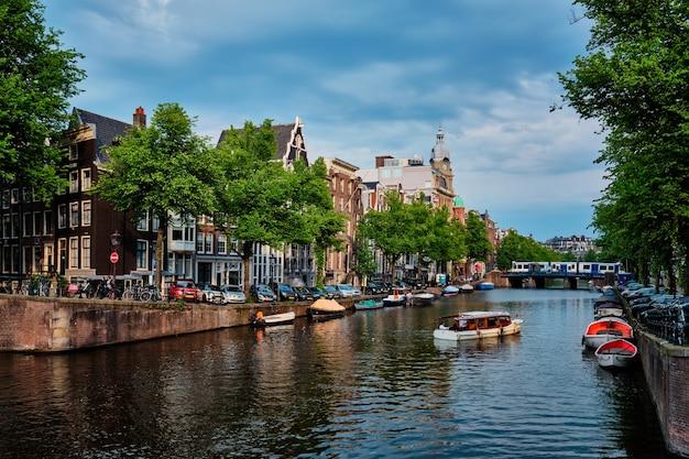 Amsterdamski kanał widokowy z mostem i starymi domami