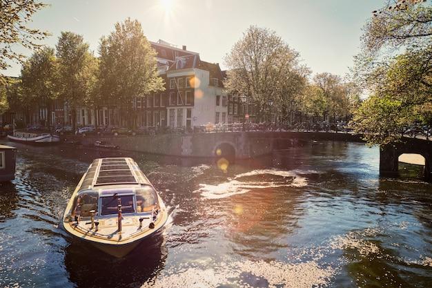 Amsterdamski kanał z łodzią turystyczną