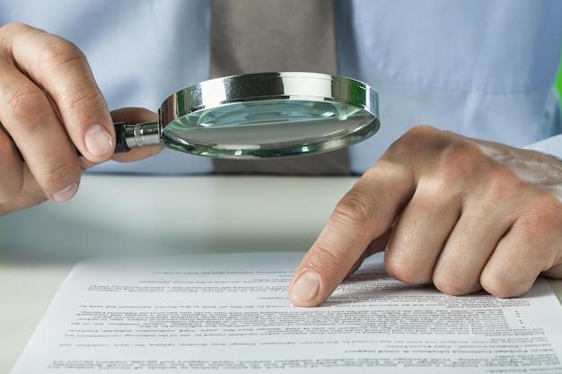 Analityka biznesowa i statystyki. biznesmen z raportem za pomocą lupy.
