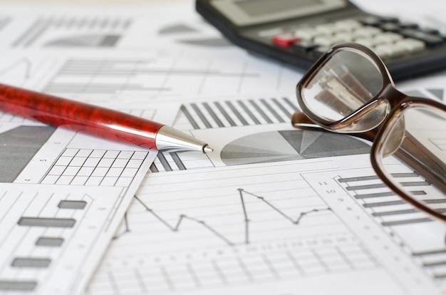 Analityka biznesowa, wykresy i wykresy. pióro, okulary, kalkulator.