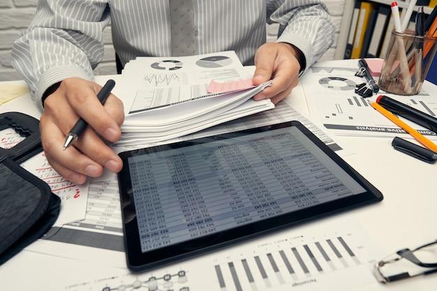 Analiza biznesowa i koncepcja rachunkowości - biznesmen pracy z dokumentem, arkuszem kalkulacyjnym, za pomocą kalkulatora, komputera typu tablet. zbliżenie biurko.