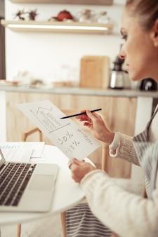 Analiza biznesowa. inteligentna biznesowa dama liczy przychodzące z jej przedsiębiorstwa siedzącego przy laptopie.