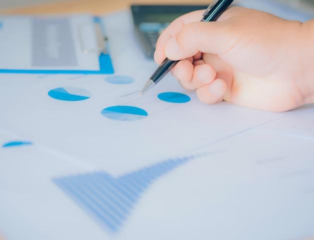 Analiza biznesowa - kalkulator, arkusz, wykresy (raport biznesowy) i dłoń analityka