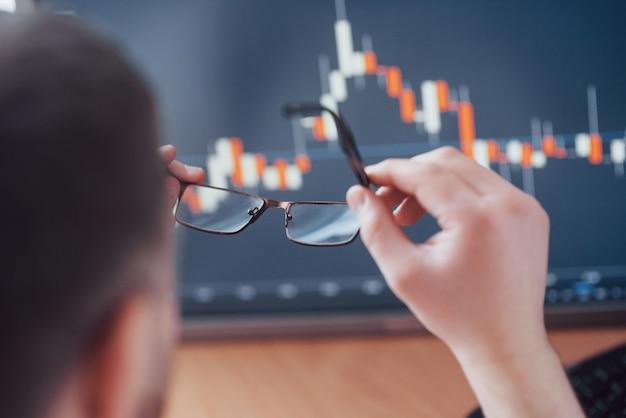 Analiza danych. zamyka up młody biznesmen który trzyma szkła i patrzeje gff podczas gdy pracujący w kreatywnie biurze