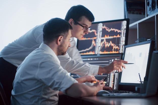 Analiza danych. zbliżenie: zespół młodych firm pracujących razem w biurze kreatywnym, podczas gdy młoda kobieta, wskazując piórem na dane przedstawione na wykresie.