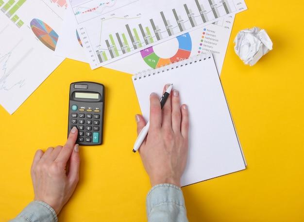 Analiza ekonomiczna. kobiece dłonie liczą kalkulator na żółtym tle z notatnikiem, wykresami i wykresami.