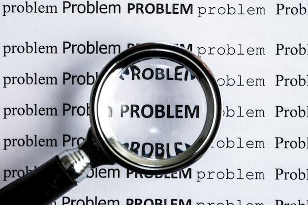"""Analiza koncepcyjna istniejących problemów. słowo """"problem"""" drukowane na papierze pod szkłem powiększającym."""