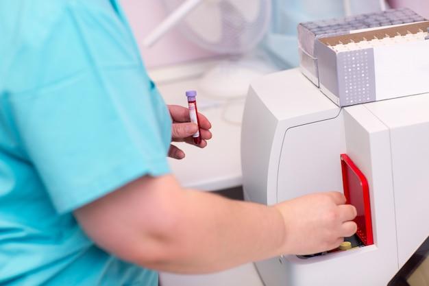 Analizator krwi asystent laboratoryjny w laboratorium medycznym trzyma w ręce probówkę z krwią i osoczem i dokonuje analizy.