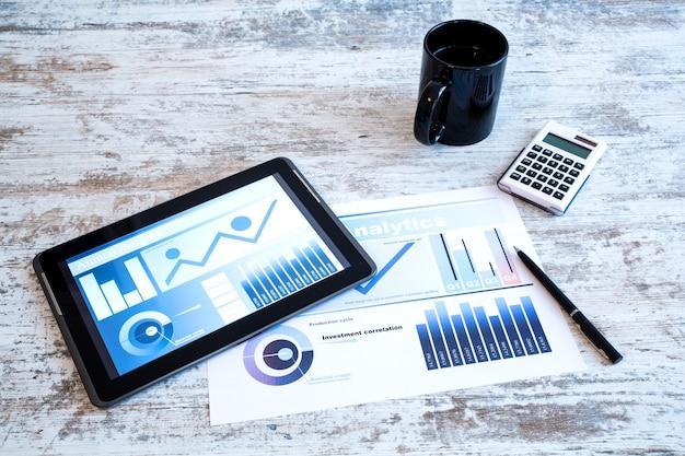 Analizy biznesowe na drewnianym biurku z komputerem typu tablet.
