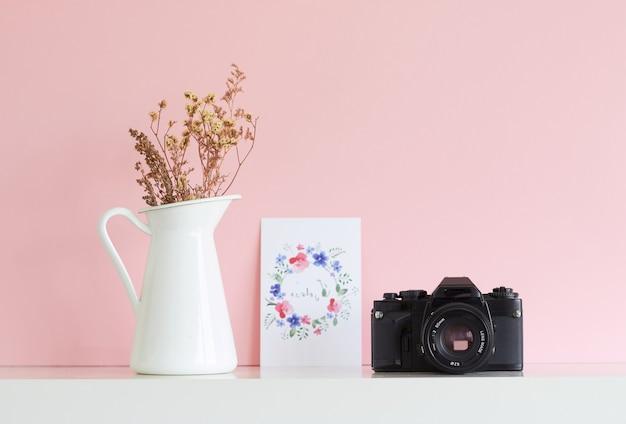 Analogowa pocztówka z kwiatowym aparatem i biały wazon z suchymi kwiatami na różowym tle