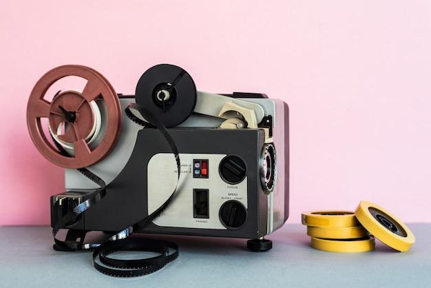 Analogowe urządzenie audio i taśmy umieszczone na szarym stole w pobliżu różowej ściany w domu
