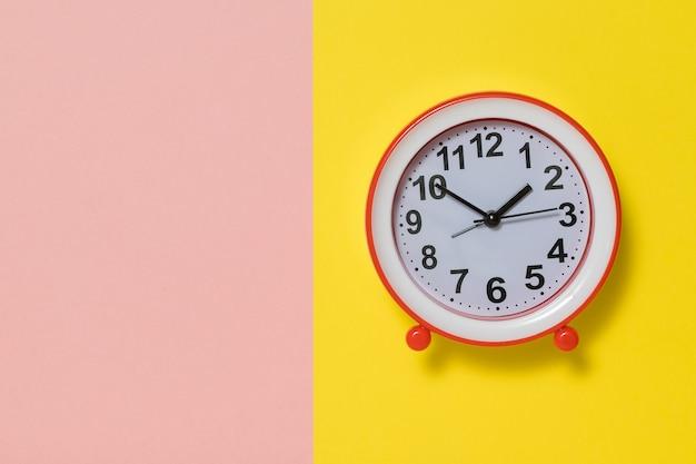 Analogowy budzik ze strzałkami na żółtym i różowym tle. klasyczny zegar analogowy.