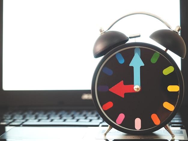 Analogowy zegar retro kolorowa igła na klawiaturze laptopa białego ekranu rozmycia tła