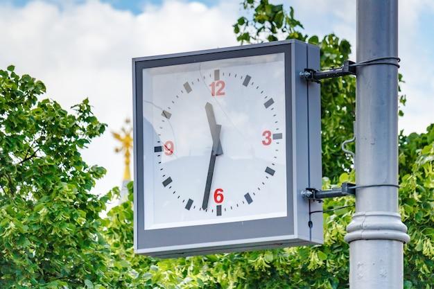 Analogowy zegar uliczny wiszący na słupie