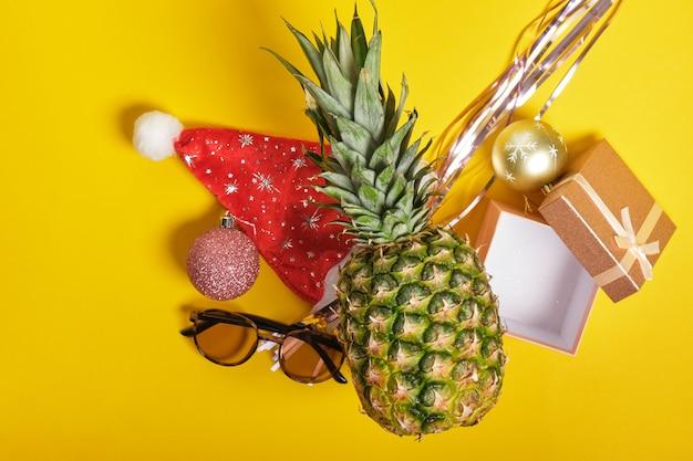 Ananas, czapka mikołaja i okulary przeciwsłoneczne, świąteczny wystrój na żółtym tle