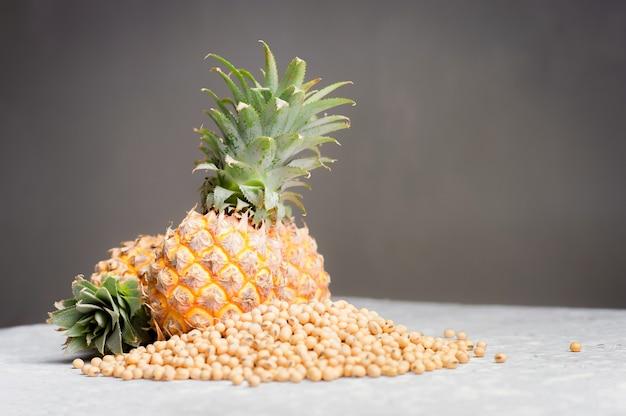 Ananas i soja na pustym bielu cementu stole nad popielatym cementem izolujemy tło