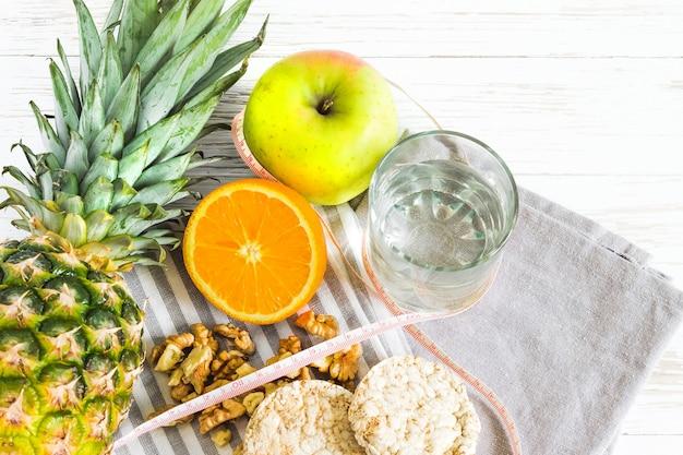 Ananas, jabłko, dokrętki na talerzu na błękitnym tle