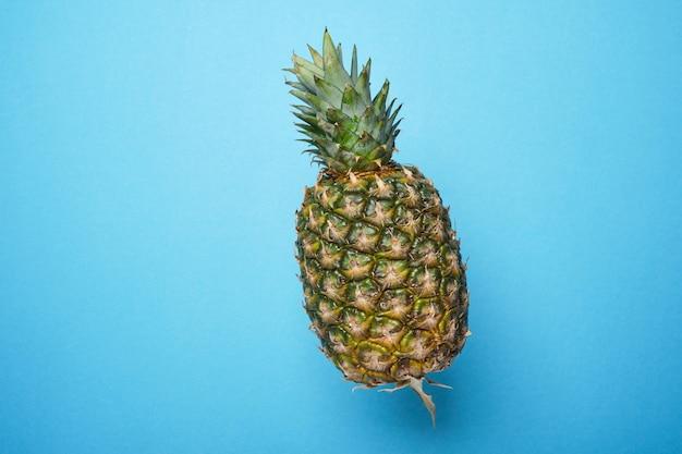 Ananas na niebieskim tle. koncepcja lato. kopia przestrzeń, minimalizm.