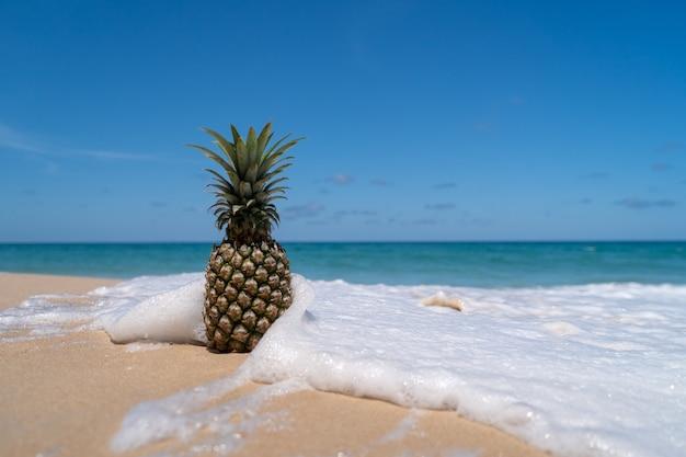 Ananas na piasku z pluskiem wody morskiej na koncepcji lato błękitne niebo.