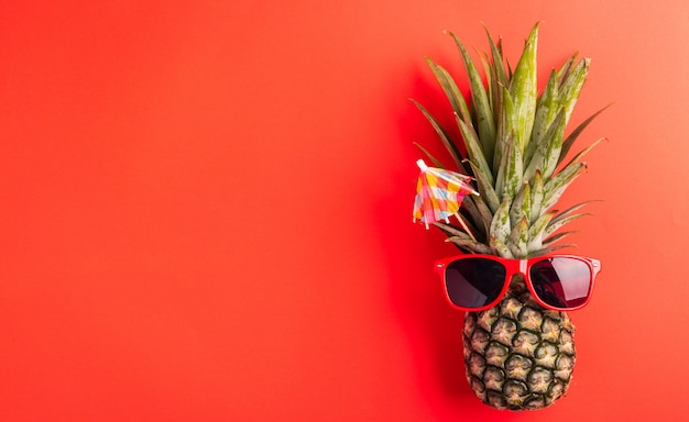 Ananas nosi czerwone okulary przeciwsłoneczne na czerwono
