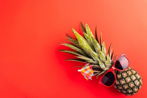 Ananas nosi czerwone okulary przeciwsłoneczne