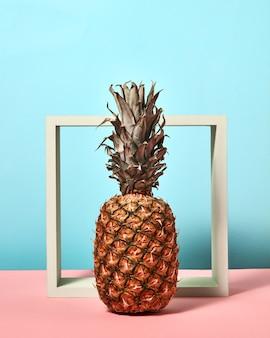 Ananas owoce tropikalne pojedyncze stojące przed białą kwadratową ramką na bichromii różowo-niebieskim tle. naturalne jedzenie.