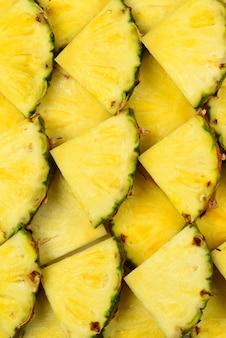 Ananas soczyste plasterki żółte tło. widok z góry.