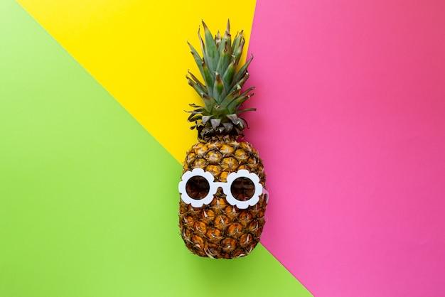 Ananas w białych okularach przeciwsłonecznych na kolorowym tle, kreatywnie lata pojęcie