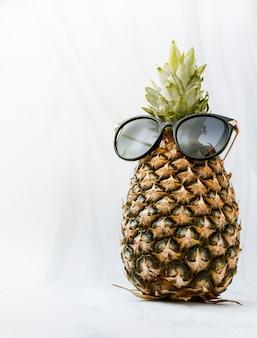 Ananas w okularach przeciwsłonecznych na białym tle