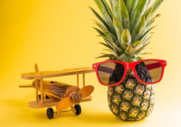 Ananas w okularach przeciwsłonecznych stoi z modelem samolotu