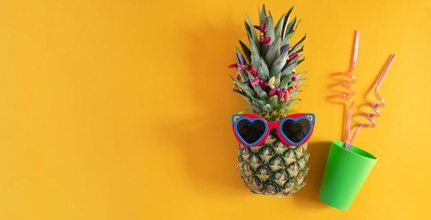 Ananas w okularach przeciwsłonecznych w kształcie serca i zielonym plastikowym kubku na żółtym tle