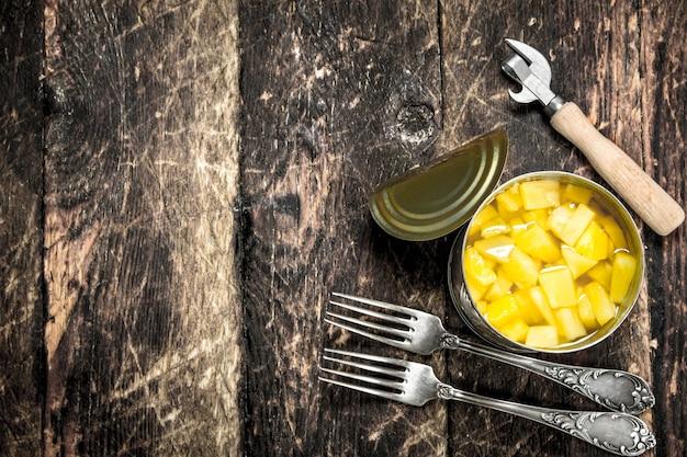 Ananas w puszce w puszce z widelcem i otwieraczem. na drewnianym tle.