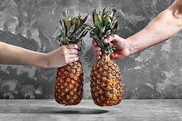 Ananas w rękach na tle cementu. dostawa jedzenia