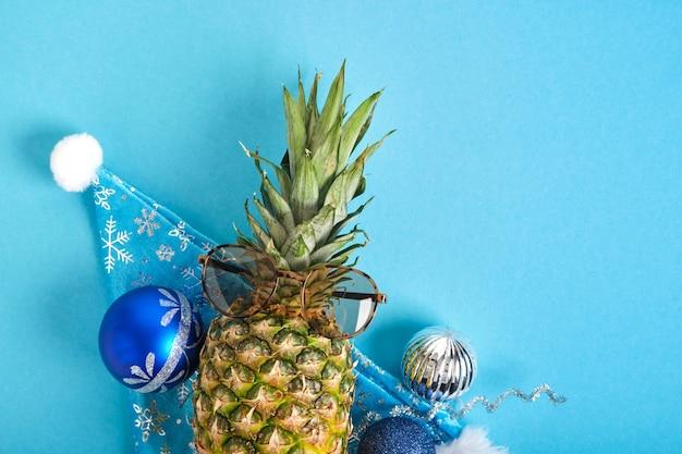 Ananas w santa hat i okulary przeciwsłoneczne, świąteczny wystrój na niebieskim tle, ferie zimowe w koncepcji tropików