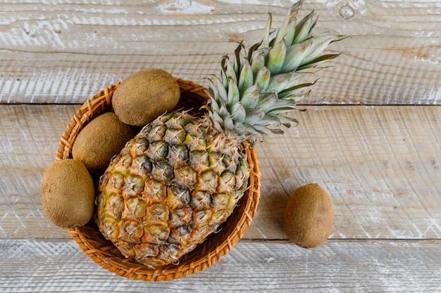 Ananas w wiklinowym koszu z owocami kiwi na powierzchni drewnianych