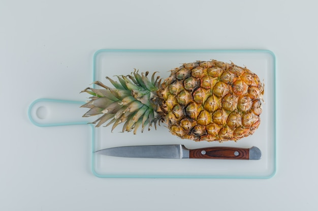 Ananas z nożem na białej desce do krojenia