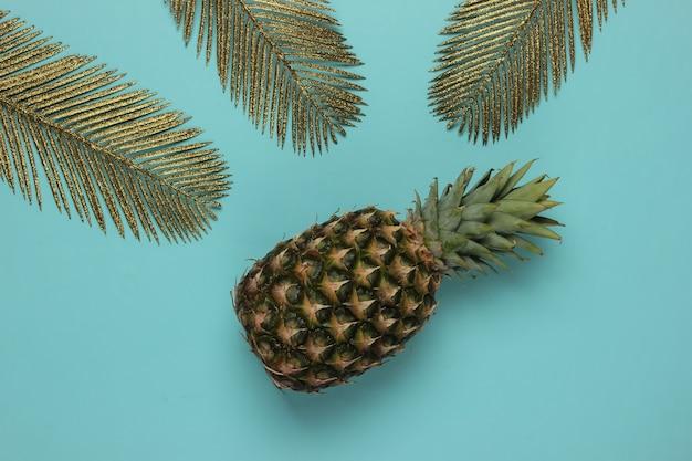 Ananas ze złotymi liśćmi palm na niebieskim tle pastelowych. koncepcja tropikalna. widok z góry