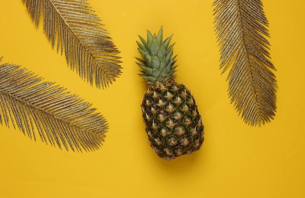 Ananas ze złotymi liśćmi palmowymi na żółtym tle. koncepcja tropikalna. widok z góry