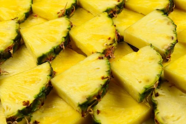 Ananasowy soczysty plasterki żółte tło. widok z góry.