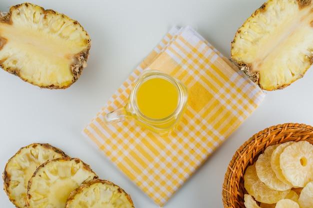 Ananasy z sokiem i kandyzowanymi krążkami na ręczniku kuchennym w kratkę
