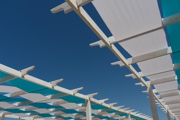 Anapa. region krasnodar - 14 maja 2021: zadaszenia, altany, pomalowane w paski niebiesko-białe, konstrukcje architektoniczne wykonane z drewna na plaży nad morzem czarnym